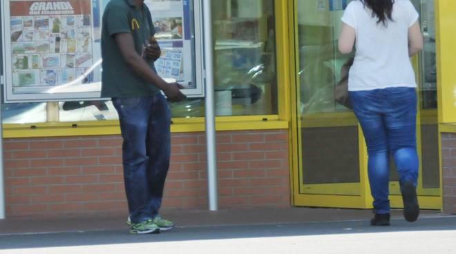 Migrante chiede elemosina davanti supermercato